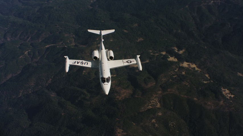 4K stock footage aerial video of panning across mountains to reveal a Learjet C-21 in Northern California Aerial Stock Footage | WAAF02_C019_0117JN_S003