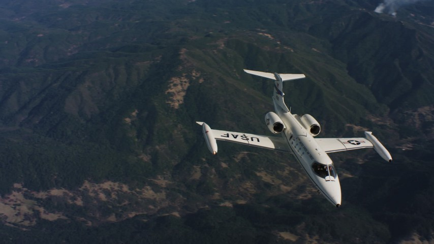 4K aerial stock footage video of tracking a Learjet C-21 in flight over mountains in Northern California Aerial Stock Footage | WAAF02_C020_0117TR