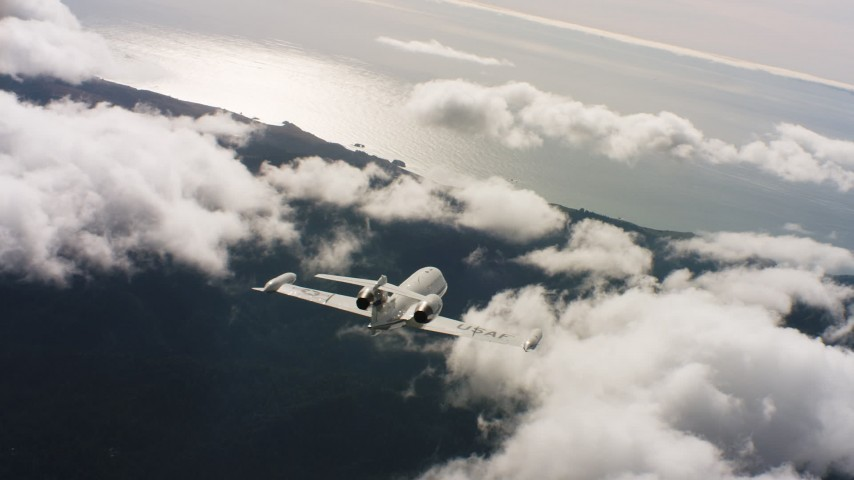 4K stock footage aerial video of a Learjet C-21 weaving back and forth over clouds near the ocean in Northern California Aerial Stock Footage | WAAF02_C029_0117CV_S002