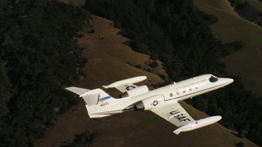 4K aerial video of a Learjet C-21 flying over mountains and out of frame in Northern California Aerial Stock Footage | WAAF02_C044_0117QQ