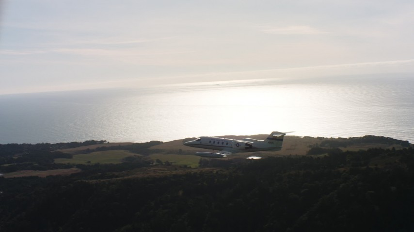 4K aerial stock footage video of a Learjet C-21 flying over hills on the coast in Northern California Aerial Stock Footage WAAF02_C048_0117VK | Axiom Images