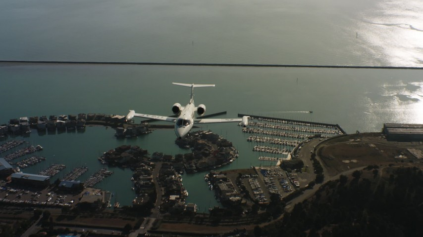4K aerial video of a reverse view of a Learjet C-21 flying over the bay in Northern California Aerial Stock Footage | WAAF02_C054_0117PF_S000