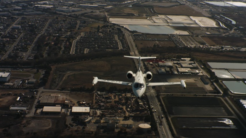 4K stock footage aerial video of a reverse view of a Learjet C-21 flying over industrial buildings in Northern California Aerial Stock Footage | WAAF02_C055_01177K
