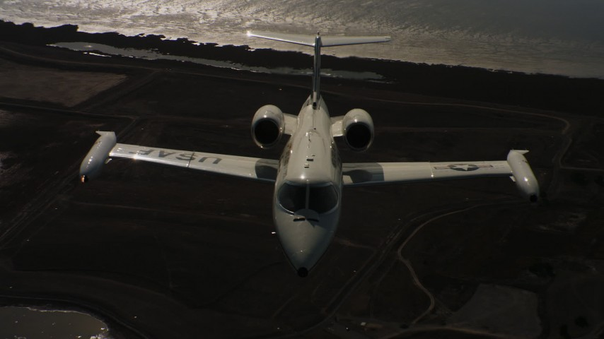 4K stock footage aerial video of a reverse view of a Learjet C-21 entering frame and flying over bay, Northern California Aerial Stock Footage | WAAF02_C059_01174D