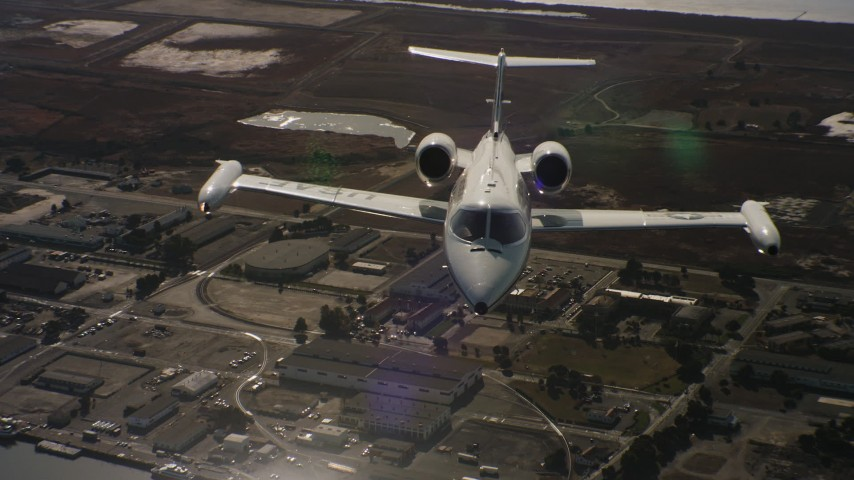 4K stock footage aerial video tilt from industrial buildings to reveal a Learjet C-21 in Northern California Aerial Stock Footage | WAAF02_C059_01174D_S000