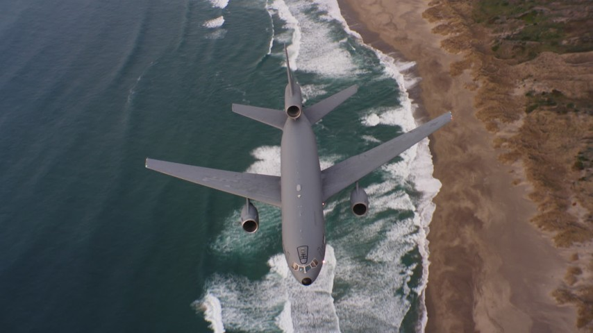 4K stock footage aerial video of a reverse view of a McDonnell Douglas KC-10 flying over beaches in Northern California Aerial Stock Footage | WAAF03_C055_01189Q