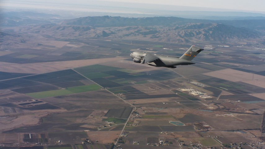 4K aerial video of a Boeing C-17 over farmland with cargo door open in Northern California Aerial Stock Footage WAAF05_C026_0118U2