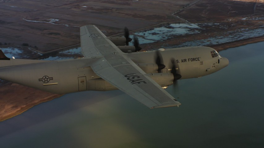 4K stock footage aerial video of revealing a Lockheed Martin C-130J flying over wetlands in Northern California, sunset Aerial Stock Footage | WAAF06_C007_0119WJ