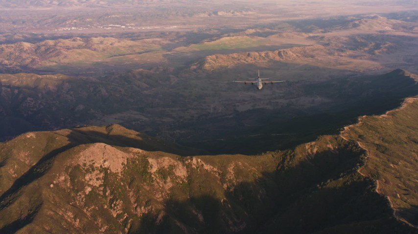 4K stock footage aerial video of a reverse view of Lockheed Martin C-130J over mountains at sunset in Northern California Aerial Stock Footage WAAF06_C051_0119NW | Axiom Images