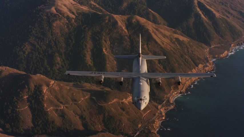 4K aerial video reverse view of a Lockheed Martin C-130J flying over mountains near coast of Northern California Aerial Stock Footage WAAF06_C052_0119WK