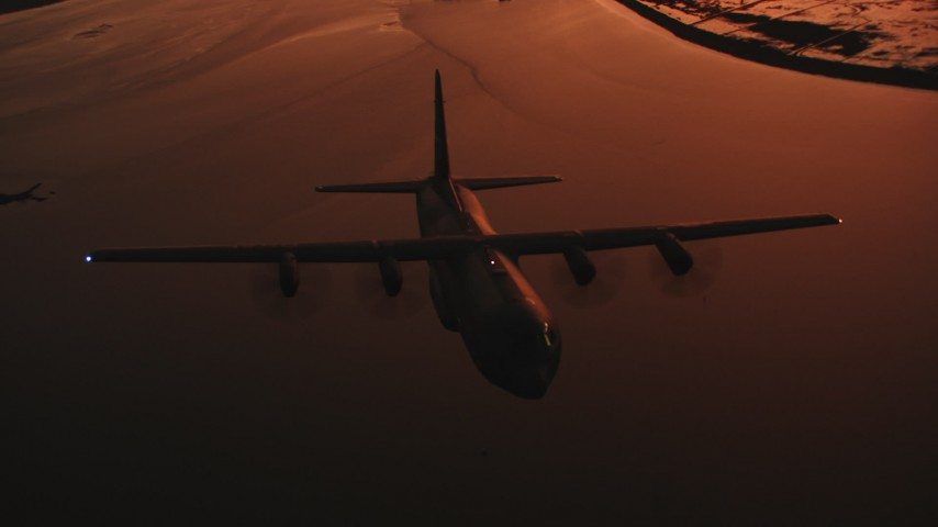 4K stock footage aerial video reveal a Lockheed Martin C-130J flying over a bay at sunset, Northern California Aerial Stock Footage | WAAF06_C091_0119E1