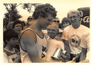 1980-07-26-Downtown-Race organzier George Taylor and George Buie Reeve present Terry Fox with honorary items as he runs through Barrie during Ten MIlion Dollar Miracle of Hope Run across Canada (A)