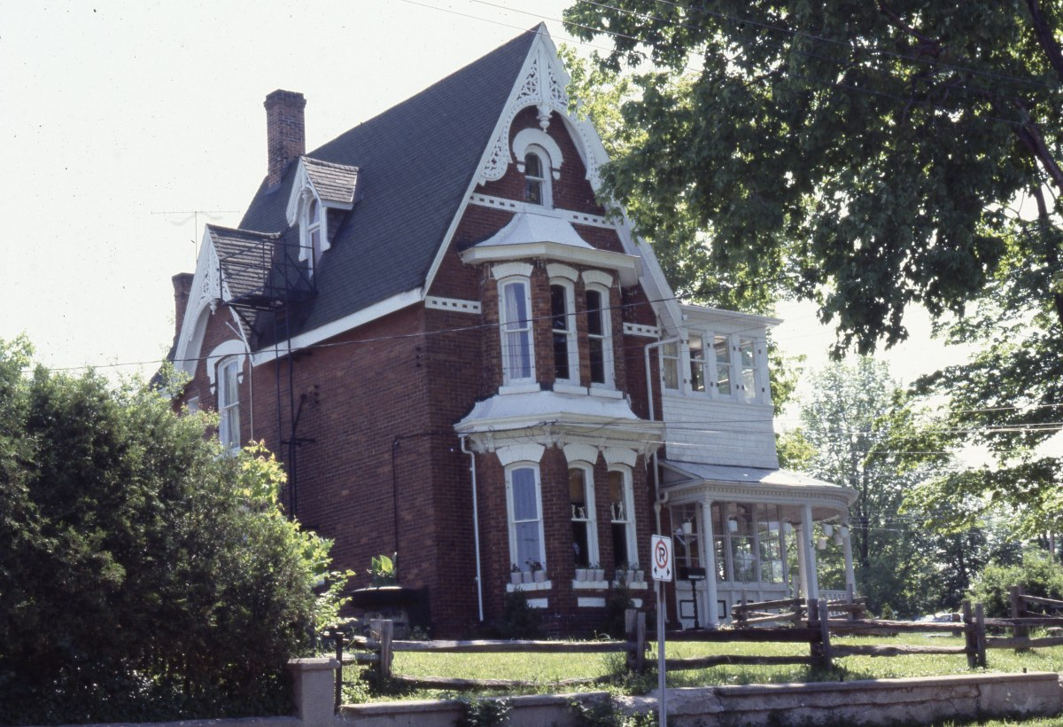 A red-bricked old home with a small front yard.