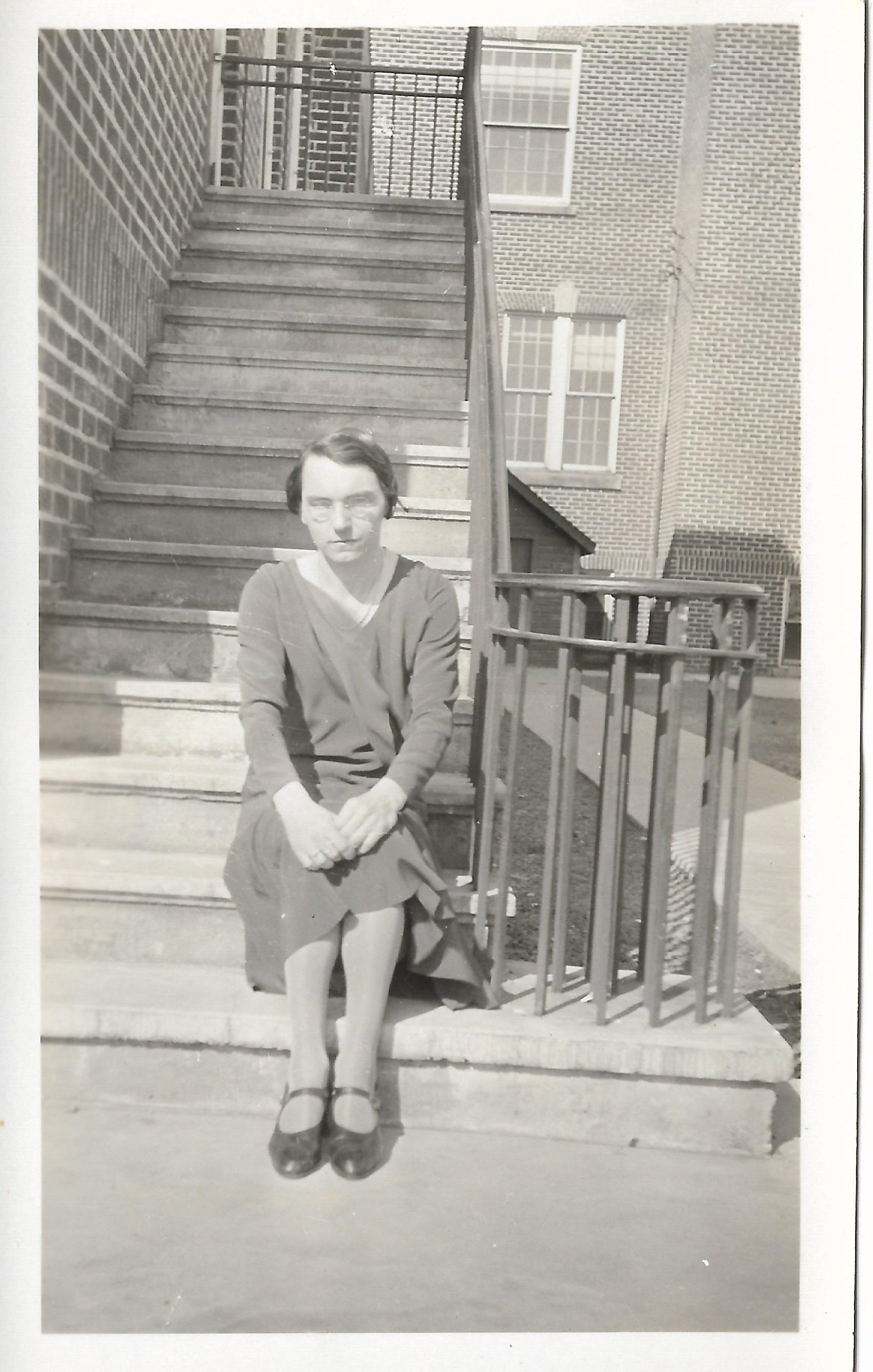 Ms. Riley, the latin teacher at Barrie Central Collegiate, sits outside the school on a staircase.
