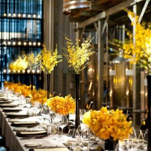 Many place settings and flowers adorn a long table set-up in the Press Alley space