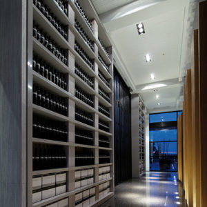 Wine bottles stacked on a shelf in long hallway