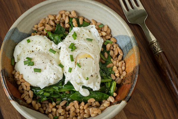 This healthy Poached Egg Grain Bowl features fresh spinach and bok choy, cooked brown rice, green onion, and an Asian-inspired seasoning.