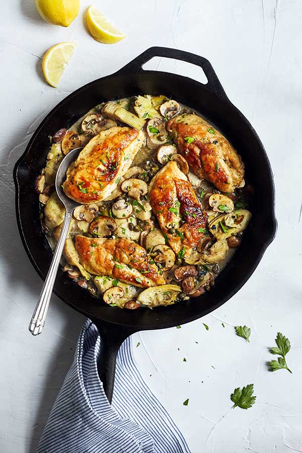 This healthier chicken piccata recipe is prepared in the classic style and topped with flavorful mushrooms, artichokes, and capers.