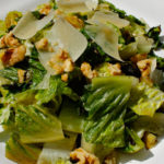 This easy Grilled Romaine salad is an ideal BBQ side with grilled romaine, crunchy walnuts, and shaved parmesan topped with a tangy lemon dijon dressing.