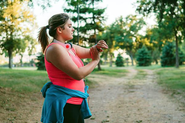 Overweight runner checking smart watch.