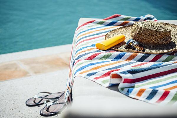 Sunscreen, hat, sunglasses on a towel by the pool