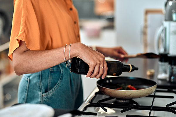 Woman pouring oil into a pan on stove
