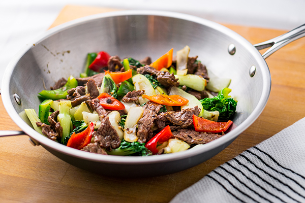 Wok stir-fried beef and vegetable on cutting board.