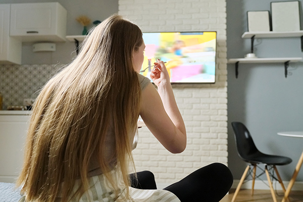 Young woman sitting at home watching tv and eating