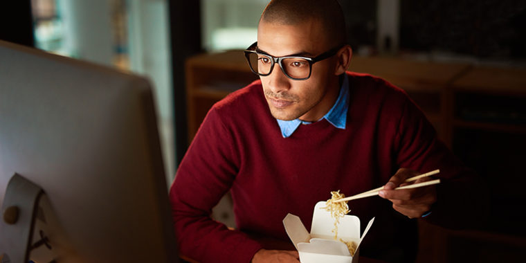 Is Eating Before Bed Bad? - man eating dinner at computer