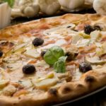 Making an artisan Artichoke Pizza at home has never been easier with this recipe featuring artichoke hearts, sliced mushrooms, and fresh olives.