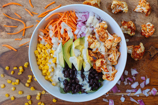 This barbecued cauliflower salad features smokey barbequed florets, black beans, corn kernels, ripe avocado, and a healthier ranch dressing.