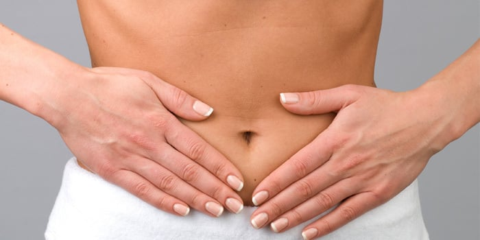 woman with bad digestion holding her stomach