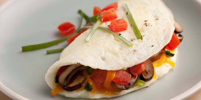 Healthy egg white omelet recipe with mushrooms, tomatoes, and cheddar cheese.