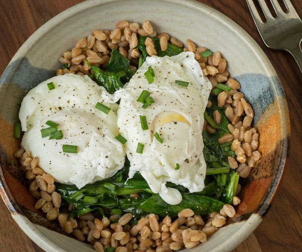 Healthy rice bowl recipe with brown rice, spinach, bok choy, and poached eggs