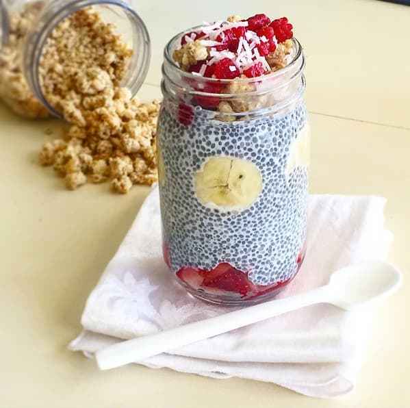 Meal prep snacks chia pudding with banana, strawberries, and granola in a Mason jar