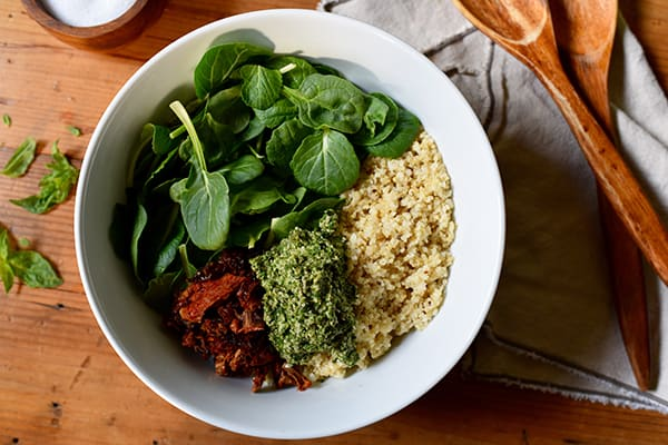 This Quinoa with Sun-Dried Tomatoes and Pesto recipe is a bowl of superfood that tastes incredible made with hemp seeds, fresh baby spinach, and basil.