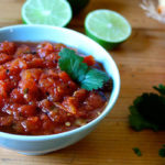 This rich, smoky roasted tomato salsa can be made in minutes featuring chopped cilantro, fresh lime juice, garlic, onion, and fiery jalapeño peppers.
