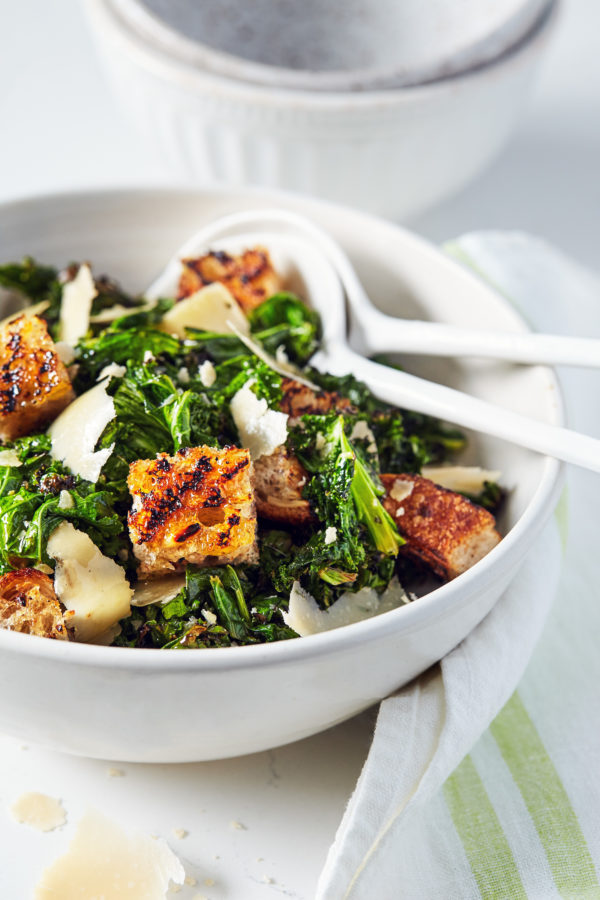 Healthier Caesar Salad - Grilled Kale Salad with Croutons and Parmesan Cheese in a bowl