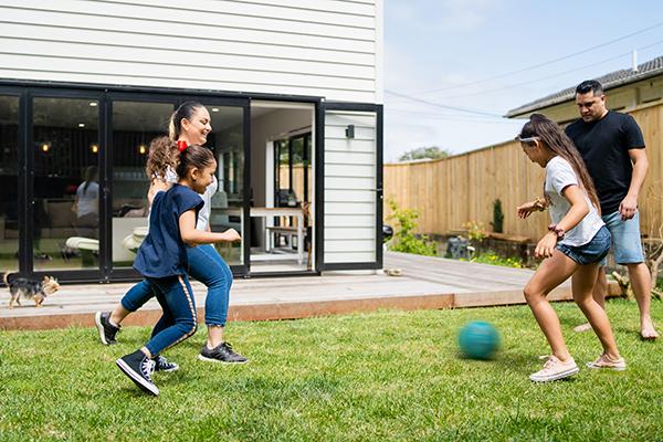 Famille jouant au football à l'extérieur