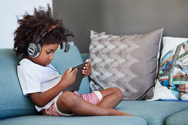 Boy sitting on couch with headphones and tablet