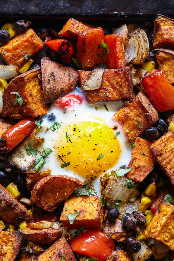This fragrantly spiced Sweet Potato Hash recipe features oven-baked eggs, cumin, smoked paprika, and is topped with fresh cilantro.