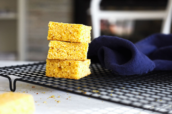 Classic cornbread fresh from the oven, sliced and stacked on a cooling rack.