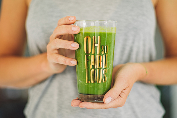 Glass of green smoothie with greens supplement