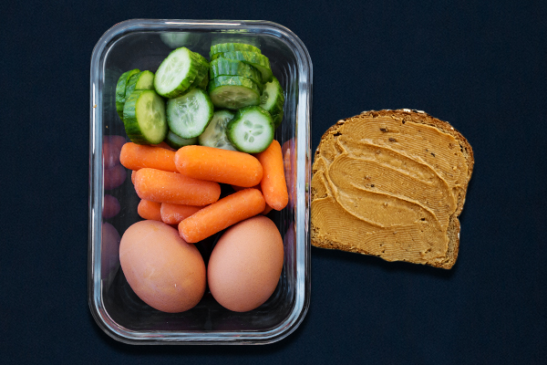 Pre-workout meal for 80 Day Obsession with hard-boiled eggs, cucumber slices, baby carrots and peanut butter toast.