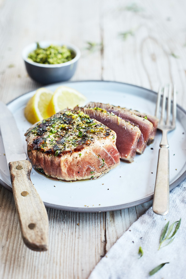 Herb and Garlic Grilled Tuna Steaks with lemon on a platter with fork and knife on a wooden table.