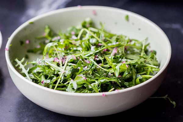 Arugula salad in a bowl with light dressing