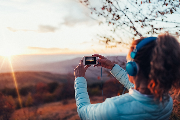 Woman taking photo of a sunset