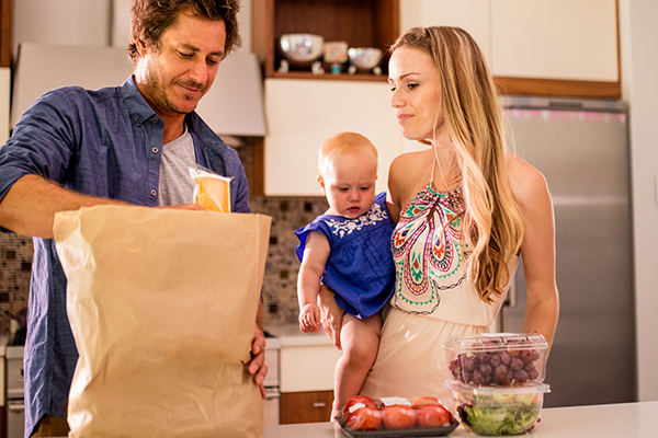 Man, woman with baby unpacking groceries