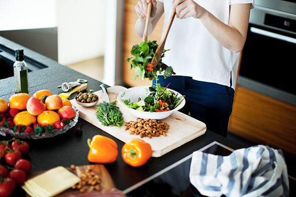 Woman tossing healthy salad