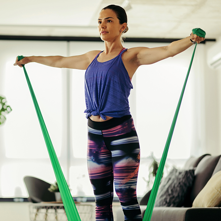 Woman using resistance band at home